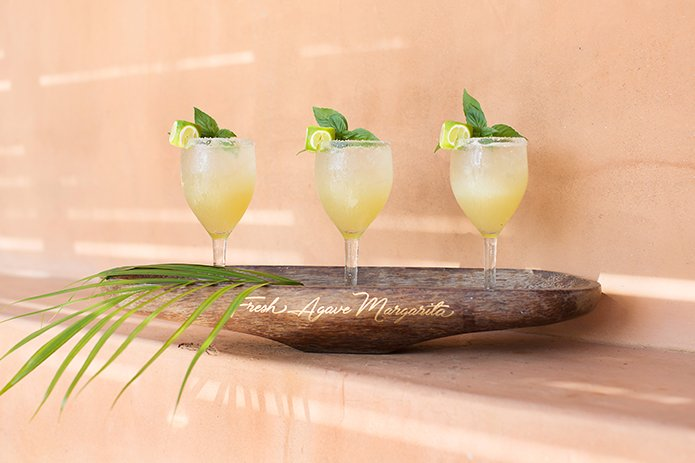San Miguel beach wedding photo shoot margaritas with lime and green floral accents served on dark brown wood platter for serving cocktail hour with guests wedding photo idea for signature drinks