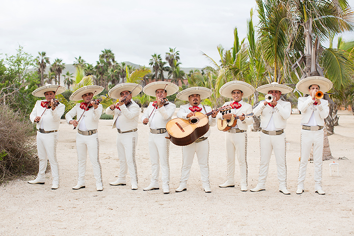 San Miguel beach wedding photo shoot mariachi band wearing all white with sombreros and red accent scarves playing the guitar and different instruments wedding band photo idea