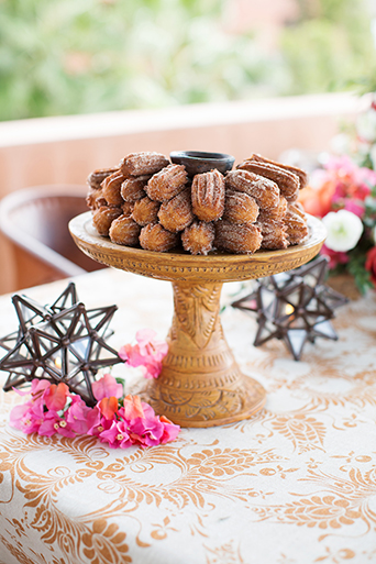 San Miguel beach wedding photo shoot mini cinnamon churro desserts served on brown platter on top of table with white and brown tablecloth and pink floral decor small desserts wedding photo idea
