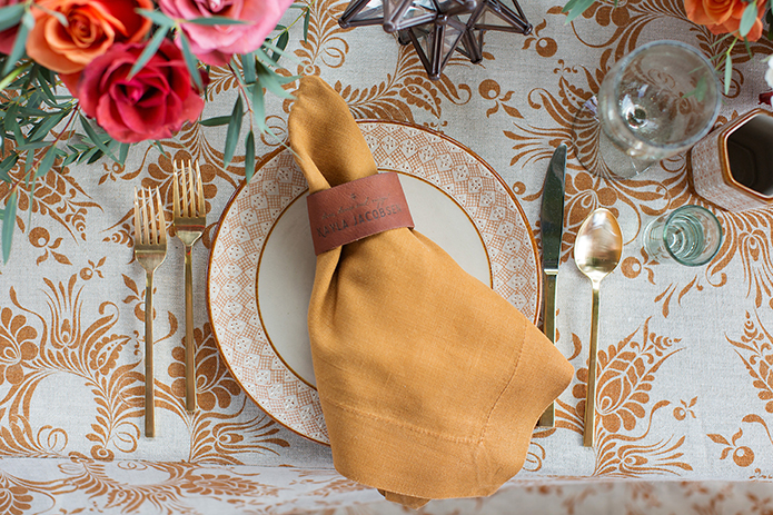 San Miguel beach wedding photo shoot white place setting with gold napkin and brown napkin ring gold silverware on top of white and brown patterned tablecloth reception table wedding photo idea