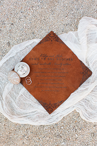 San Miguel beach wedding photo shoot printed vows for bride and groom on dark brown wood with black writing laying on the white sand wedding photo idea for ceremony vows with bride and groom
