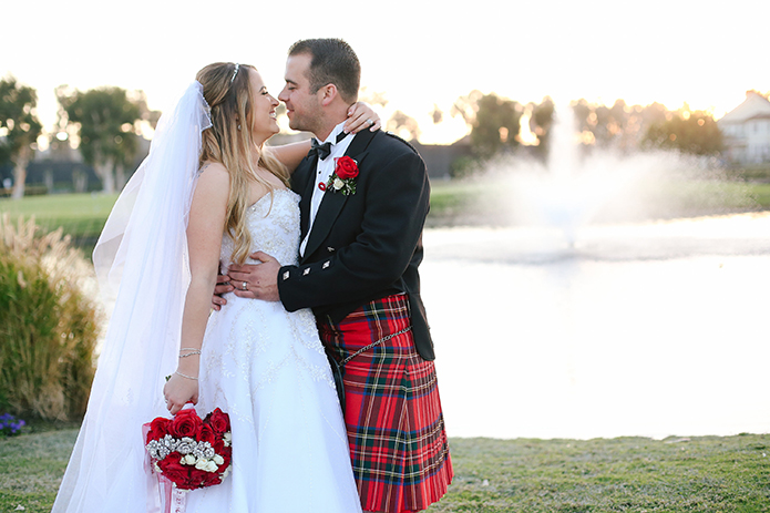 Seacliff huntington beach wedding bride strapless sweetheart neckline ball gown with crystal beaded belt with detail on top with beaded headband and long veil and red and white floral bridal bouquet and groom red and blue plaid kilt with black jacket with button decor and white dress shirt with black bow tie