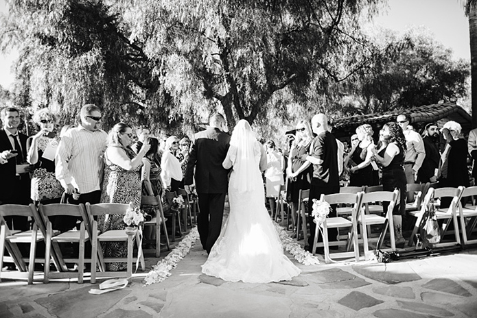 Rustic Leo carillo ranch wedding bride strapless lace gown with long lace detail veil walking down with aisle with dad black suit and black and white wedding photo idea