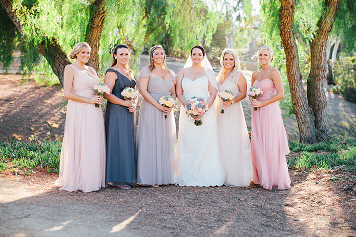 Rustic Leo carillo ranch wedding bride strapless lace gown with long lace detail veil holding white and pink succulent and floral bridal bouquet with bridesmaids long pink and grey dresses with floral bouquets