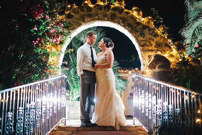 Rustic Leo carillo ranch wedding bride strapless lace gown standing in walkway under brick arch with groom heather grey suit with white dress shirt and long black skinny tie with no jacket and hands in pockets at night with lights