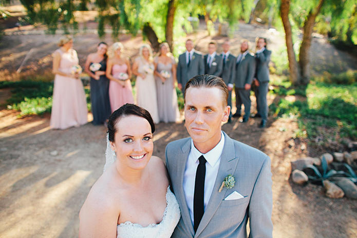 Rustic Leo carillo ranch wedding bride strapless lace gown with long lace detail veil holding white and pink succulent and floral bridal bouquet with bridesmaids mix matched pink and grey long dresses with groom heather grey suit with long black skinny tie and groomsmen charcoal grey suits with long black skinny ties