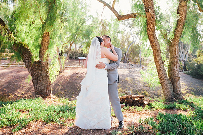 Rustic Leo carillo ranch weddinggroom heather grey suit with white dress shirt and long black skinny tie with floral boutonniere with bride strapless lace gown with long lace detail veil bride and groom kissing after first look
