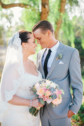 Rustic Leo carillo ranch wedding bride strapless lace gown with long lace detail veil and white and pink succulent and floral bridal bouquet with groom heather grey suit with white dress shirt and long black skinny tie with matching pocket square and succulent boutonniere