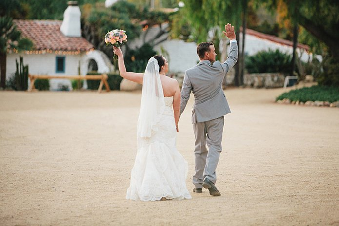 Rustic Leo carillo ranch wedding bride strapless lace gown with long lace detail veil holding hands and walking with groom heather grey suit with white dress shirt and long black skinny tie with arms in the air celebrating after ceremony