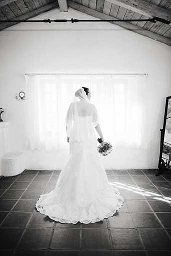 Rustic Leo carillo ranch wedding bride strapless lace gown with long lace detail veil holding white and pink succulent and floral bridal bouquet getting ready before ceremony in room black and white wedding photo idea