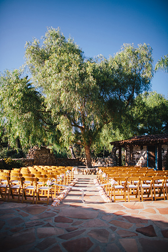 Rustic Leo carillo ranch wedding ceremony set up with brown folding chairs on stone ground with trees in background and white flower decor wedding ceremony ideas