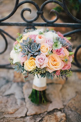 Rustic Leo carillo ranch wedding pink orange and green succulent and floral bridal bouquet with off white silk ribbon decor standing on light grey stone wall with black patterned fence background
