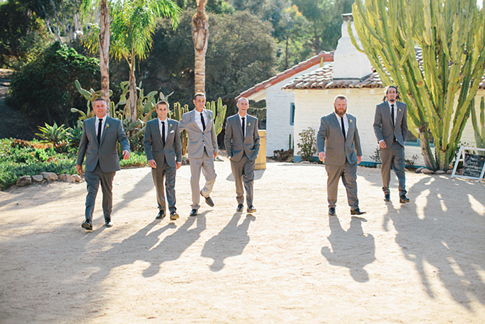 Rustic Leo carillo ranch wedding groom heather grey suit with white dress shirt and long black skinny tie with succulent floral boutonniere with groomsmen charcoal grey suits with white dress shirt and long black skinny ties walking