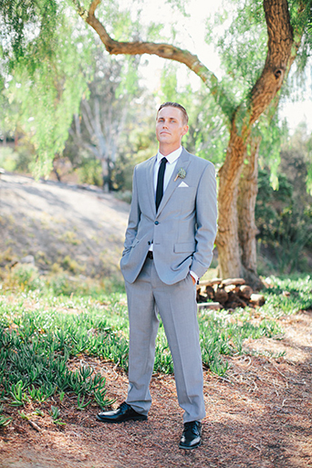 Rustic Leo carillo ranch wedding groom heather grey suit with white dress shirt and long black skinny tie with succulent boutonniere standing with hands in pockets