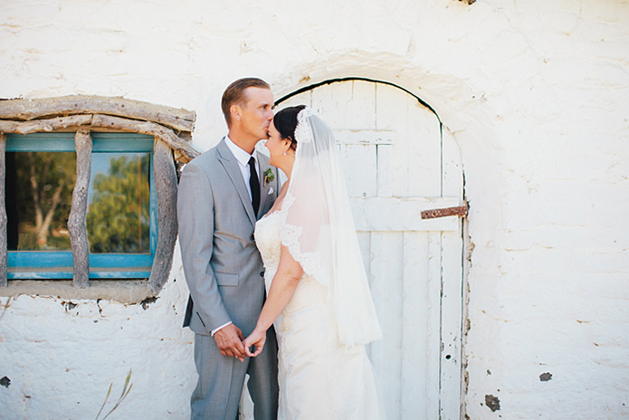 Rustic Leo carillo ranch weddingbride strapless lace gown with long lace detail veil and white and pink succulent and floral bridal bouquet with groom heather grey suit with white dress shirt and long black skinny tie with matching pocket square and succulent boutonniere
