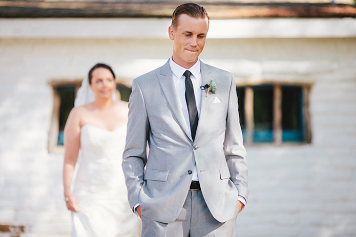 Rustic Leo carillo ranch wedding groom heather grey suit with white dress shirt and long black skinny tie with floral boutonniere with bride strapless lace gown with long lace detail veil walking behind for first look