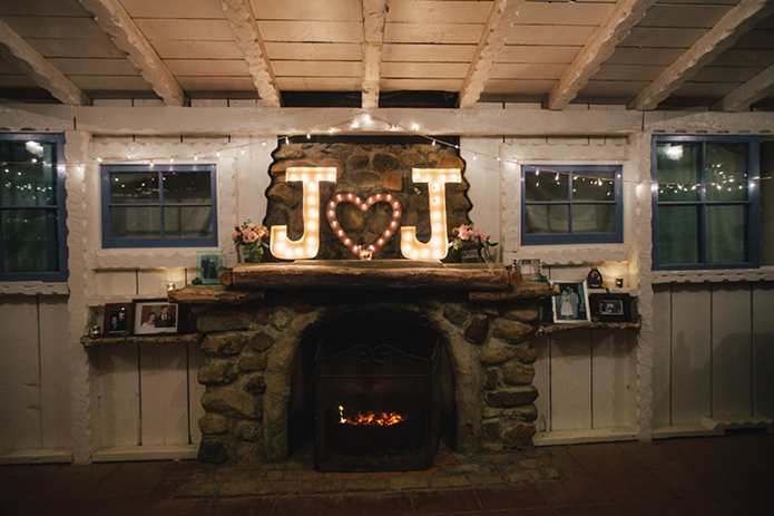 Rustic Leo carillo ranch wedding reception decor brick fireplace with bride and groom's initials marquee letters with heart in the middle for rustic reception decor wedding ideas