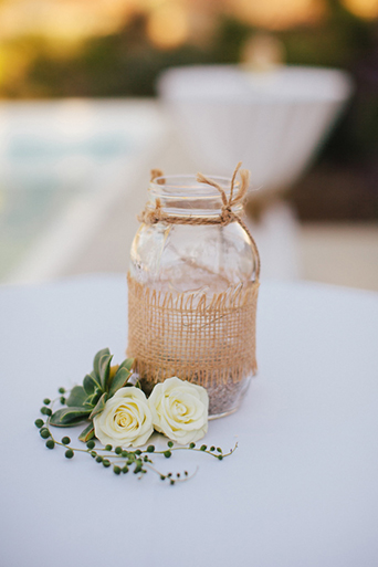 Rustic Leo carillo ranch wedding white table linen set up with clear mason jar and brown woven decor on top with white flowers and succulent decor on white table wedding decor ideas
