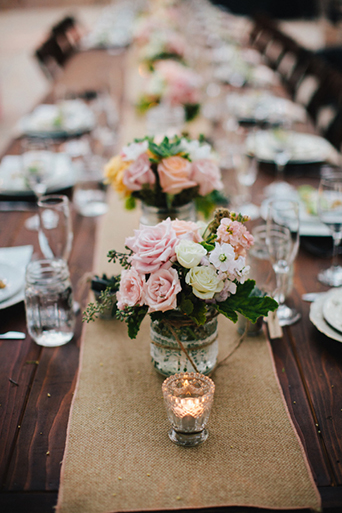 Rustic Leo carillo ranch wedding brown wood reception table set up with light brown table runner and white place settings with light pink orange and green succulent floral centerpiece with small succulent decor