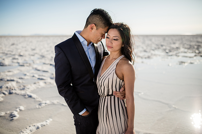Bonneville Salt Flats outdoor natural engagement shoot bride black stripped and tan gown with plunging neckline holding onto groom navy tuxedo jacket with black lapel and light blue dress shirt with no tie and dark blue jeans