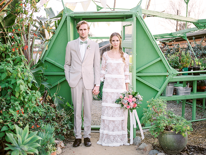 Greenhouse styled summer garden wedding shoot in San juan Capsitrano bride lace gown with sleeves and small ruffle accents and groom tan suit with white dress shirt and matching vest with black dress shoes and mint green bow tie with white and green floral boutonniere and green florals in background