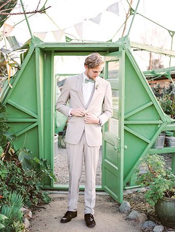 Greenhouse styled summer garden wedding shoot in San Juan Capistrano groom wearing tan suit with white dress shirt and matching vest with black dress shoes and mint green bow tie and white and green floral boutonniere button jacket