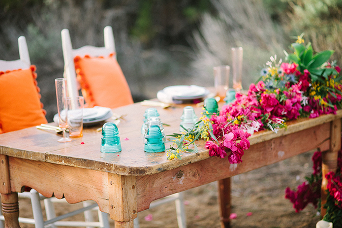 Anza valley rustic outdoor wedding at the alpaca farm brown wood table with pink and green flower decor with candles and white chairs with orange pillows