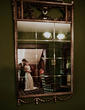 Jewel toned styled wedding shoot at the christmas house bride strapless lace gown with ruffles and crystal beading detail on top with groom burgundy tuxedo with white dress shirt and long black tie with dark red floral boutonniere reflection in mirror