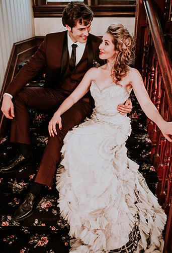Jewel toned styled wedding shoot at the christmas house bride strapless lace gown with ruffles and crystal beading detail on top with groom burgundy tuxedo with white dress shirt and long black tie with dark red floral boutonniere sitting on floral print stairs