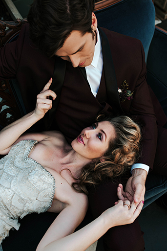 Jewel toned styled wedding shoot at the christmas house bride strapless lace gown with ruffles and crystal beading detail on top with groom burgundy tuxedo with white dress shirt and long black tie with dark red floral boutonniere