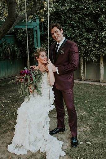 Jewel toned styled wedding shoot at the christmas house bride strapless lace gown with ruffles and crystal beading detail on top with groom burgundy tuxedo with white dress shirt and long black tie with dark red floral boutonniere bride on swing with red and pink floral boutonniere