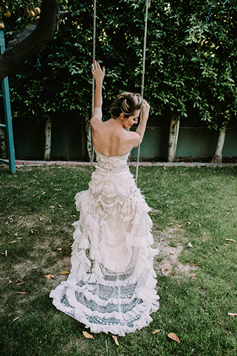 Jewel toned styled wedding shoot at the christmas house bride strapless lace and ruffled gown with crystal beading on top and wavy hair pulled to the side back of bride on swing