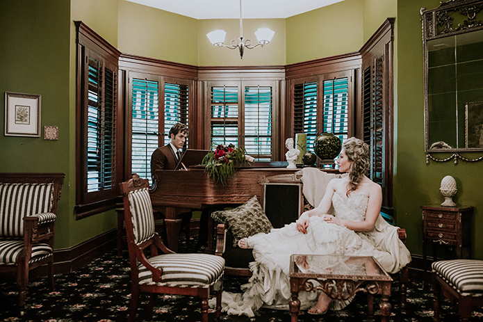 Jewel toned styled wedding shoot at the christmas house bride strapless lace gown with ruffles and crystal beading detail on top with groom burgundy tuxedo with white dress shirt and long black tie with dark red floral boutonniere playing piano and bride sitting on couch