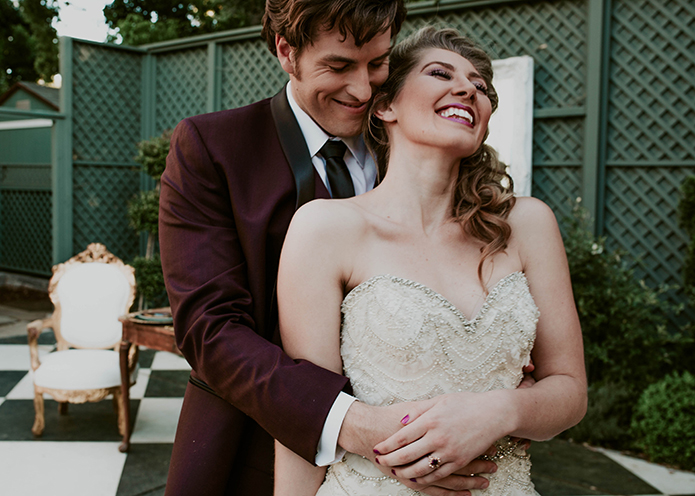 Jewel toned styled wedding shoot at the christmas house bride strapless lace gown with ruffles and crystal beading detail on top with groom burgundy tuxedo with white dress shirt and long black tie with dark red floral boutonniere hugging and laughing