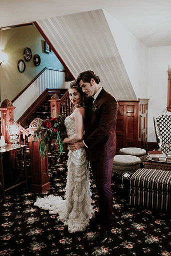 Jewel toned styled wedding shoot at the christmas house bride strapless lace gown with ruffles and crystal beading detail on top with groom burgundy tuxedo with white dress shirt and long black tie with dark red floral boutonniere hugging