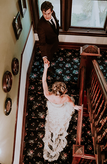 Jewel toned styled wedding shoot at the christmas house bride strapless lace gown with ruffles and crystal beading detail on top with groom burgundy tuxedo with white dress shirt and long black tie with dark red floral boutonniere walking up stairs