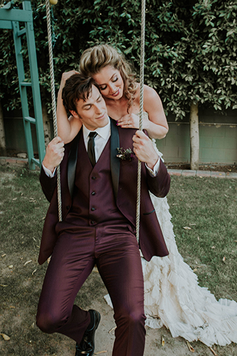 Jewel toned styled wedding shoot at the christmas house bride strapless lace gown with ruffles and crystal beading detail on top with groom burgundy tuxedo with white dress shirt and long black tie with dark red floral boutonniere on swing