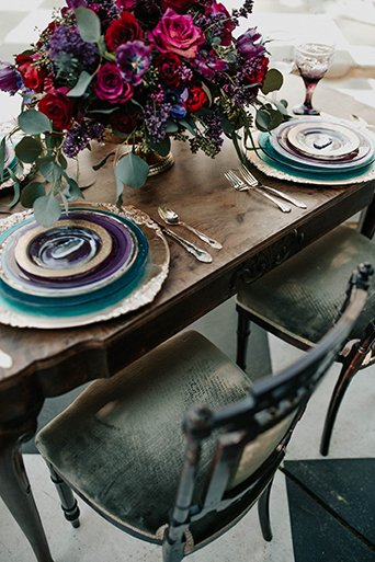 Jewel toned styled wedding at the christmas house shoot table set up with brown wood table and dark blue place settings with red and pink flower centerpieces