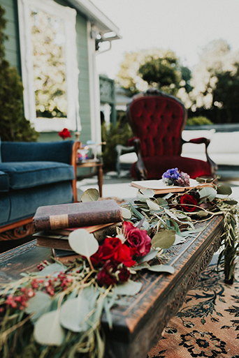 Jewel toned styled wedding at the christmas house shoot table set up with brown wood table and dark blue place settings with red and pink flower centerpieces with vintage decor
