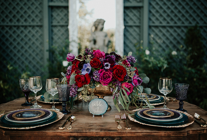 Jewel toned styled wedding shoot at the christmas house table set up with brown wood table and dark blue place settings with red and pink flower centerpieces