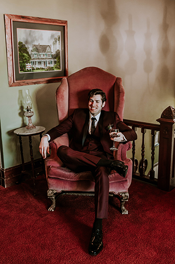 Jewel toned styled wedding shoot groom burgundy tuxedo with white dress shirt and long black tie with dark red and green floral boutonniere sitting on vintage red chair