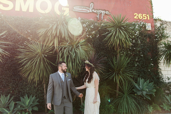 Los angeles rustic wedding at smogshoppe bride a line lace gown with short sleeves and fringe decor on top with green and white flower crown with groom grey suit with white dress shirt and matching vest with long light blue tie with white floral boutonniere