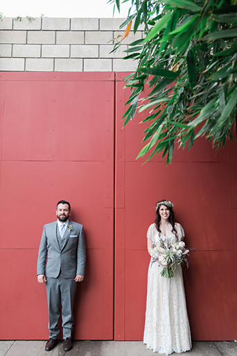 Los angeles rustic wedding at smogshoppe bride a line lace gown with short sleeves and fringe decor on top with green and white flower crown with groom grey suit with white dress shirt and matching vest with long light blue tie with white floral boutonniere standing in front of red wall