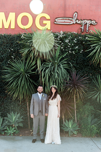 Los angeles rustic wedding at smogshoppe bride a line lace gown with lace short sleeves and fringe decor on top with green and white flower crown with groom grey suit with white dress shirt and matching vest with long light blue tie with white floral boutonniere
