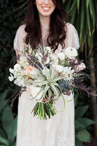 Los angeles wedding at smogshoppe bride a line chiffon gown with lace sleeves and fringe detail on top with green and white flower crown holding white and purple floral bridal bouquet