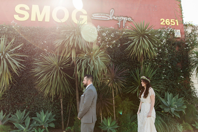 Los angeles rustic wedding at smogshoppe bride a line lace gown with short sleeves and fringe decor on top with green and white flower crown with groom grey suit with white dress shirt and matching vest with long light blue tie with white floral boutonniere bride behind groom before first look