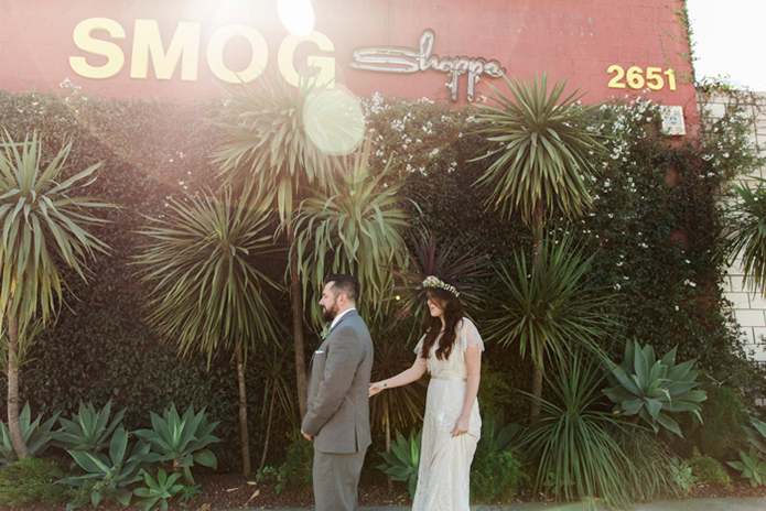 Los angeles rustic wedding at smogshoppe bride a line lace gown with short sleeves and fringe decor on top with green and white flower crown with groom grey suit with white dress shirt and matching vest with long light blue tie with white floral boutonniere bride behind groom for first look
