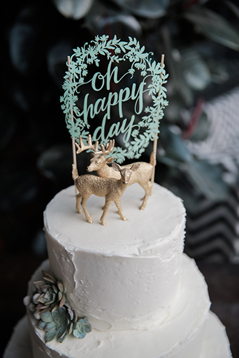 Los angeles rustic wedding at smogshoppe three tier white wedding cake with deer toppers and green happy day writing
