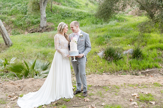 San Diego wedding at los willows bride a line lace gown with sleeves and open back design with crystal headband with groom heather grey suit with white dress shirt and blush pink bow tie with white floral boutonniere holding wedding cake on tray