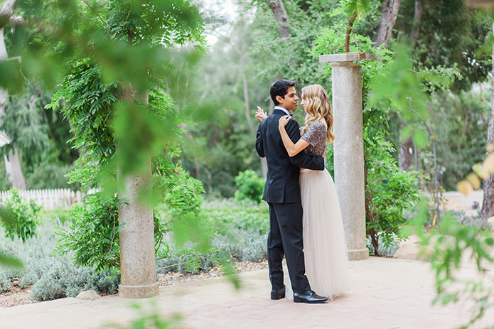 Santa barbara engagement shoot bride silver sequined crop top with long white tulle skirt with groom black tuxedo with white dress shirt and black bow tie with white pocket square dancing